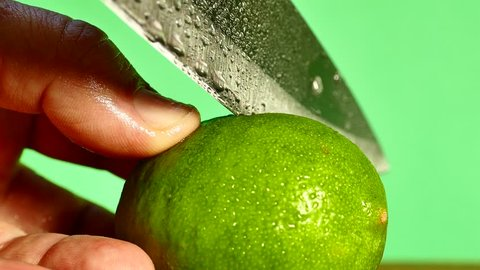 Lime green Lemon cut with a knife and squeeze out the lemon juice with his hands. Lime juice. On a green background. Green screen and chrome key.