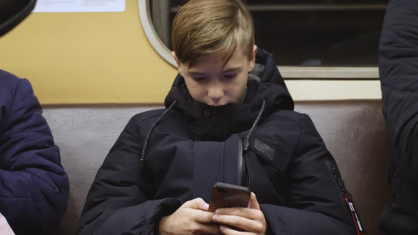The boy rides the subway and holds a smartphone in his hands. Online chatting with friends
