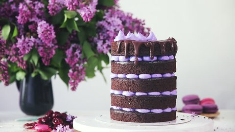 Decorating multilayered cake with lilac cream, chocolate coating and macaroon cakes. Making wedding or birthday party cake, dessert. Bouquet of lilacs in a vase is on the table.