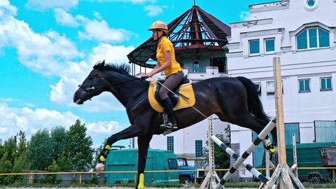 Young woman on horse jumping over obstacles. Slow motion. Training horses before the competition. Horse Racing. Horse breeding. Farm. Horseman. Rider, equestrian, jockey