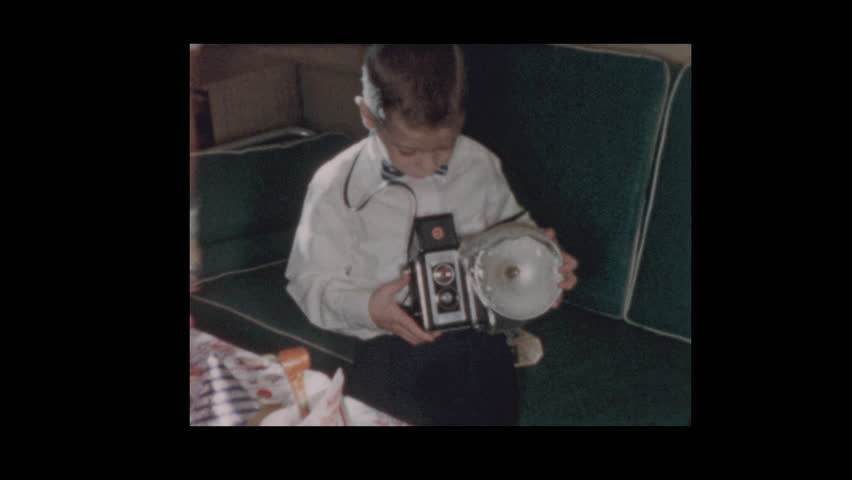 1956 Little boy dressed up in bow tie with vintage antique flash camera