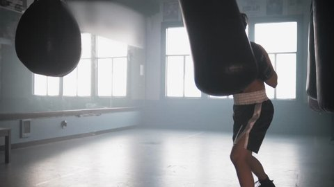 A strong, sweaty female boxer trains intensely on a punching bag in a boxing gym