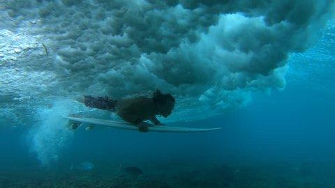 Amateur surfer does unsuccessful duck dive with short board