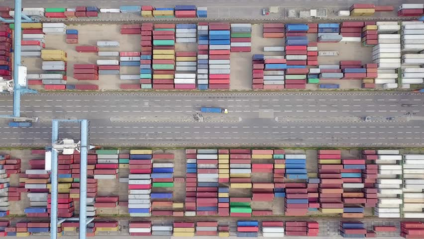 Transtainer yard - Various brands and colours of Shipping containers stacked by Transtainers (Mobile gantry cranes) off of service trucks - Top down aerial footage. | Shutterstock HD Video #1023022741