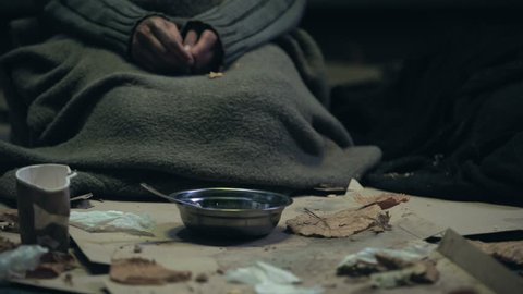 Homeless person with trembling hands greedily eating soup, dirty shelter, famine