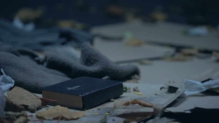 Bible lying on floor in dirty place full of garbage, hope and belief concept