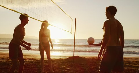 Friends playing beach volleyball at sunset, volleyball spike in slow motion cinematic