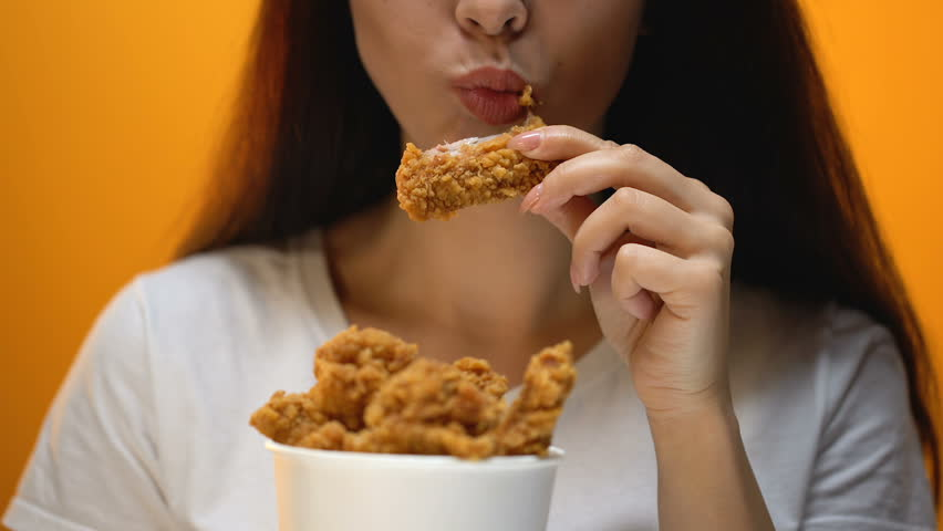 Girl eating chicken wings, high calorie food and health risks, cholesterol | Shutterstock HD Video #1023107221