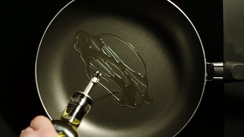 Man pouring cooking oil on the frying pan - Top View