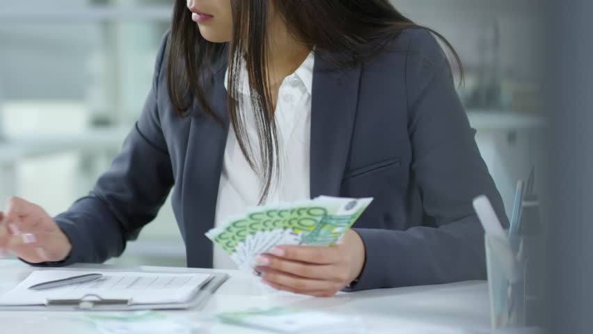 Mid-section shot of businesswoman in formal suit holding euro banknotes, using calculator and writing down on paper while working at office desk #1023117631