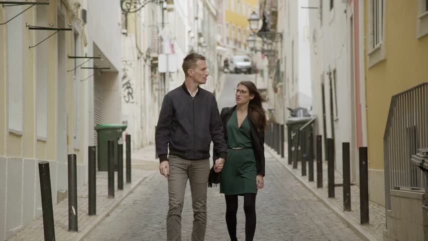 Happy young couple walking on street and looking around. Smiling couple in love walking on street and holding hands together. Relationship concept | Shutterstock HD Video #1023119371