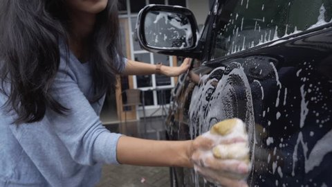portrait of beautiful young asian woman washing her car at home