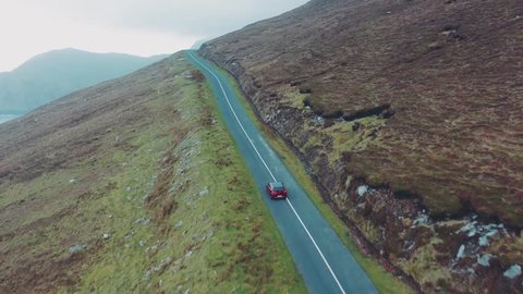 aerial view of red Toyota Auris car moving on beautiful curved coastal road. Ireland, Achill Island, 3rd of January 2019