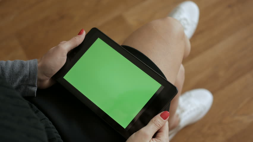 Girl using digital tablet.  Woman holding a tablet in the hands of a green screen green screen, hand of man holding mobile smart phone with chroma key green screen on white background. Technology.  #1023194641