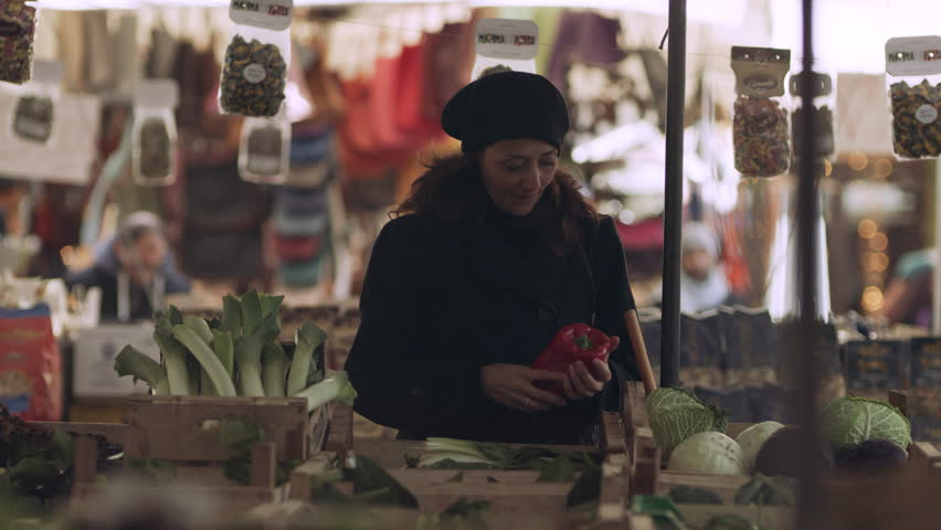 A content Italian woman walking through a busy food market looking at different fresh produce and ingredients in Rome, with soft natural lighting. Wide shot on 8k helium RED camera.