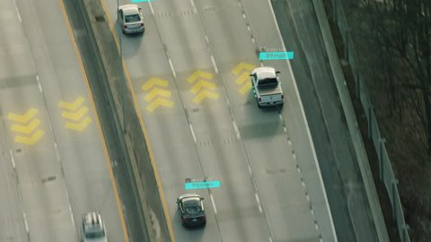 Self Driving cars driving on a highway with technology tracking them, showing speed and who is controlling the car. Visual effects clip shot on 4k RED camera.