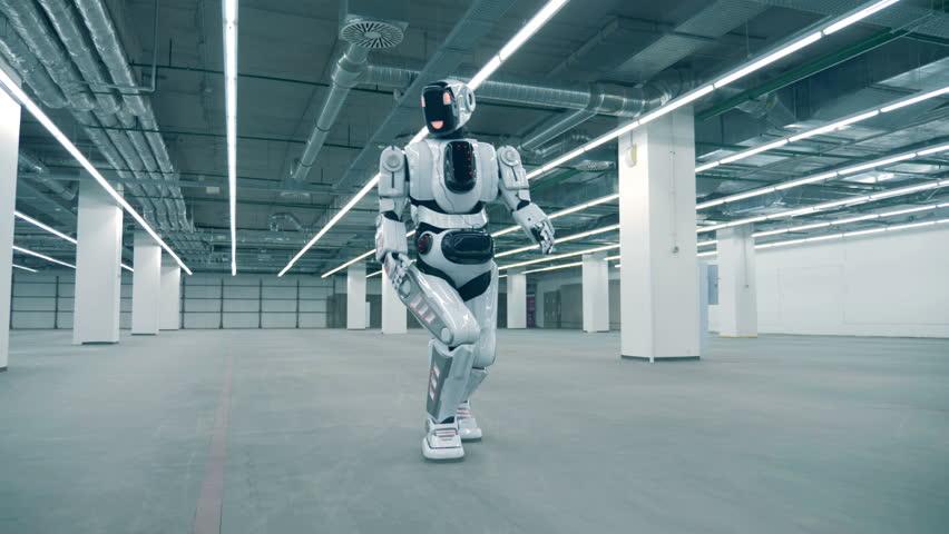 Empty spacious storage unit with a human-like cyborg walking along it | Shutterstock HD Video #1023238681