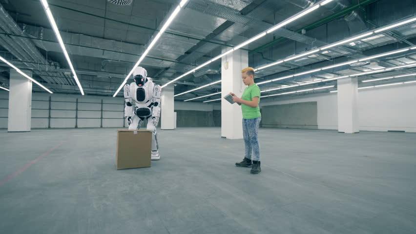 Teenage boy is guiding a robot to lift a carton box | Shutterstock HD Video #1023238921