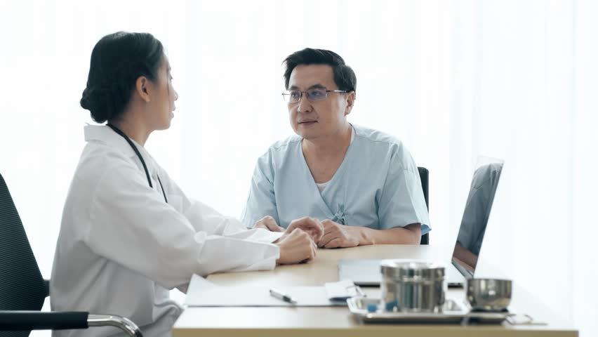 Doctor with patient. Young female medical doctor talking to a senior patient at hospital. Sharing medical test result via computer. Senior care medical and insurance concept.