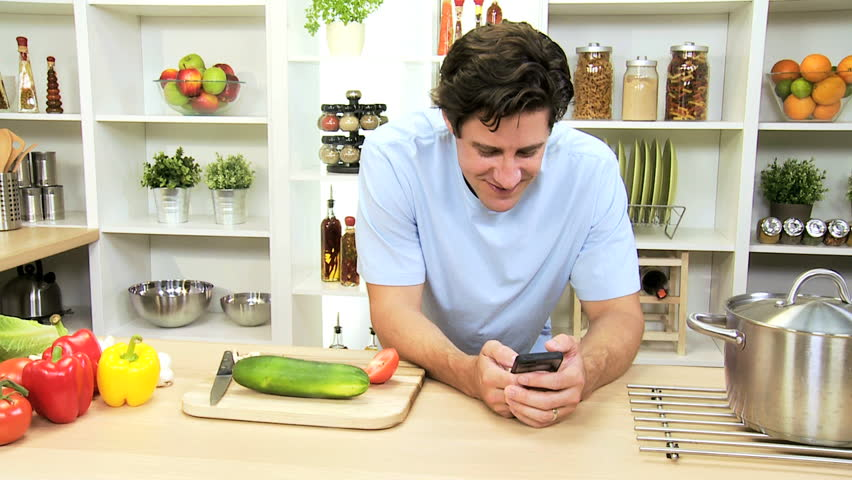 Young Caucasian male using wireless smart phone apps home kitchen to search recipes for healthy living meal with fresh organic vegetables