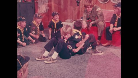 1970s: Cub scouts wrestle on floor in den. Cub scouts cheer on wrestling boys.