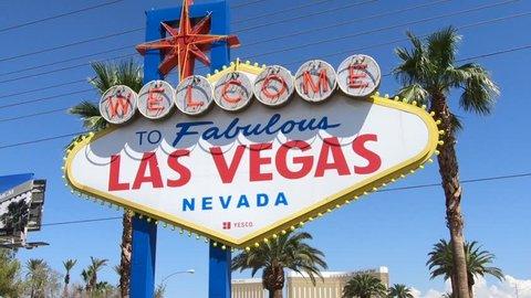 Las Vegas, Nevada, United States - September 20, 2018: the popular Las Vegas Sign. Welcome to Fabulous Las Vegas Nevada on Las Vegas Strip. Harley Davidson sign on background.