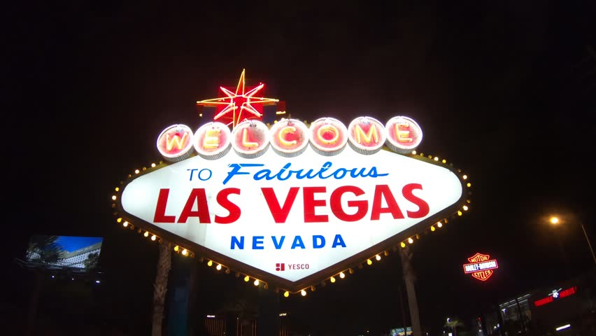 Las Vegas, Nevada, United States - September 20, 2018: the popular Las Vegas neon Sign. Welcome to Fabulous Las Vegas Nevada illuminated by night. Harley Davidson sign on background.