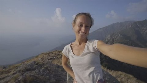 Cheerful young woman taking a selfie portrait on mountain top after hiking all the way up reaching summit; People enjoying Summer outdoor activities concept