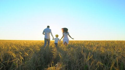happy family outdoors running on wheat field with little boy. Mother, father and son kid child having fun on summer day, enjoying nature together. health love travel summertime happy holiday happiness