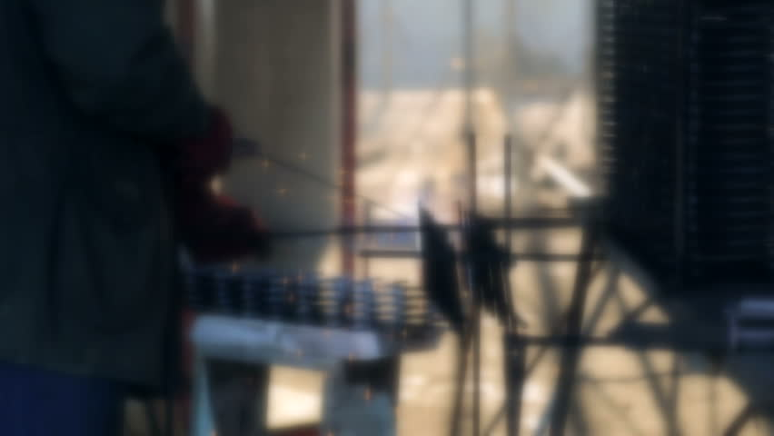 Background an employee welds a metal structure on a construction site. Construction works. Work outdoor #1023383131