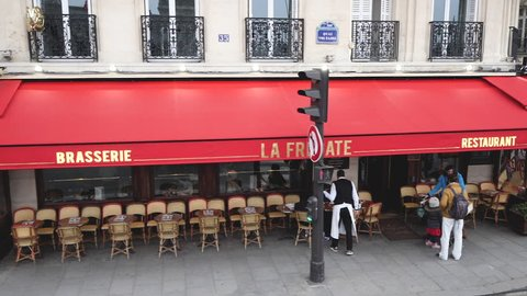 PARIS, FRANCE - CIRCA 2019: Angle Quai Voltaire elevated view aerial drone over Parisian street with crowded Cafe la Fregate - pedestrians walking and beautiful slow motion waiter taking order
