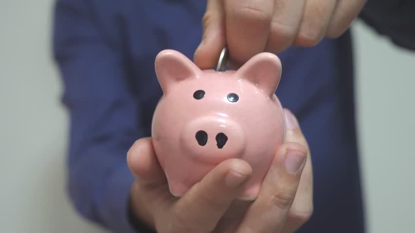 businessman makes lifestyle savings puts coins in a piggy bank. piggy bank business concept. slow motion video. saving money is an investment for the future. Banking investment and finance. hand is