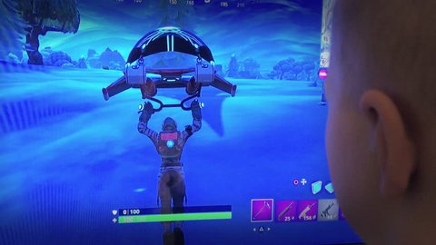 Fortnite Video Game Playing Closeup Footage. Person playing popular game with big tv screen. 30th January 2019. Finland, Espoo.