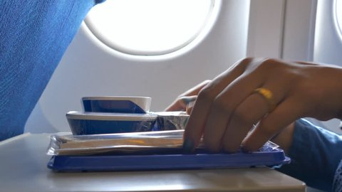 Passenger woman eats food on Board the plane. Woman eating in the airplane