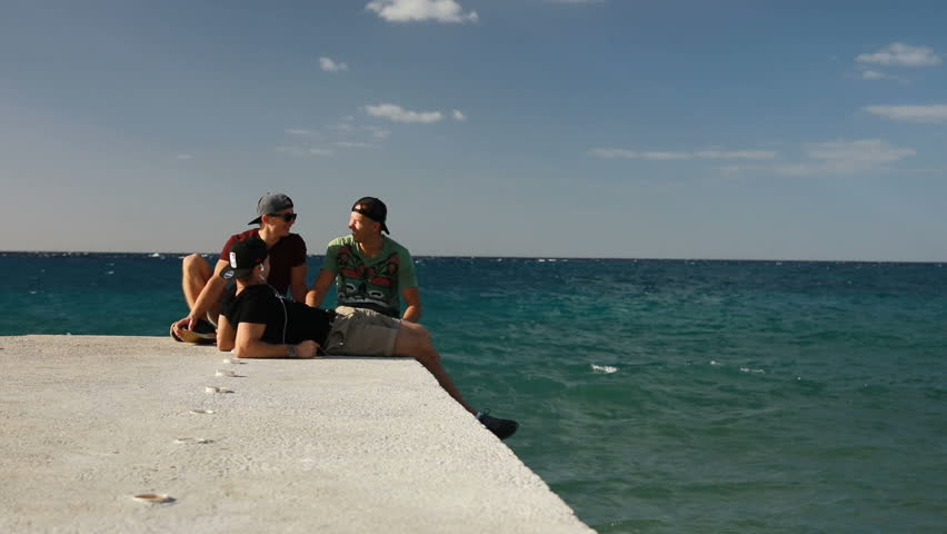COZUMEL,MEXICO,22 DECEMBER 2018:Three men friends siting on pier and talking with each other isolated Caribbean sea in Mexico. | Shutterstock HD Video #1023459451