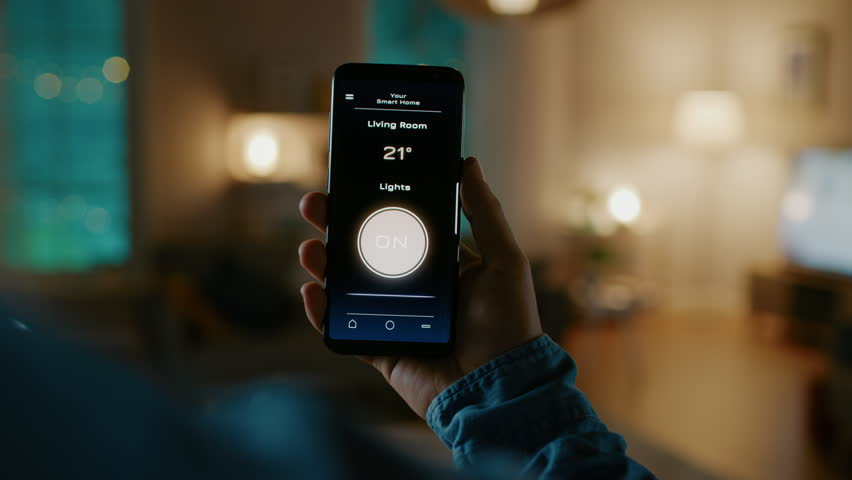 Close Up Shot of a Smartphone with Active Smart Home Application. Person is Giving a Voice Command and Light Turns On in the Room. It's Cozy Evening in the Apartment. | Shutterstock HD Video #1023495721