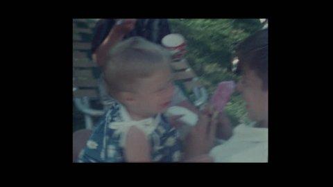 1964 Boy feeds little girl ice cream popsicle