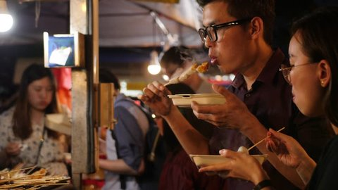 Young Couple Eating Traditional Asian Street Food Barbecue Satay on Wooden Stick at Night Market. 4K Cinematic Slowmotion Footage. 30 JAN 2019 - Kuala Lumpur, Malaysia.