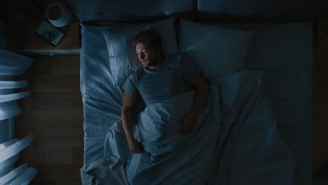 Top View of Handsome Young Man Sleeping Cozily on a Bed in His Bedroom at Nigh, He Tosses and Turns. Blue Nightly Colors with Cold Weak Lamppost Light Shining Through the Window.