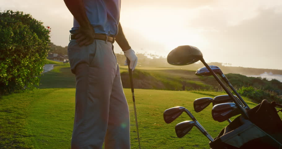 Handsome older golf stands on golf course with clubs, luxury golf detail shot, sunset ocean golf | Shutterstock HD Video #1023661621