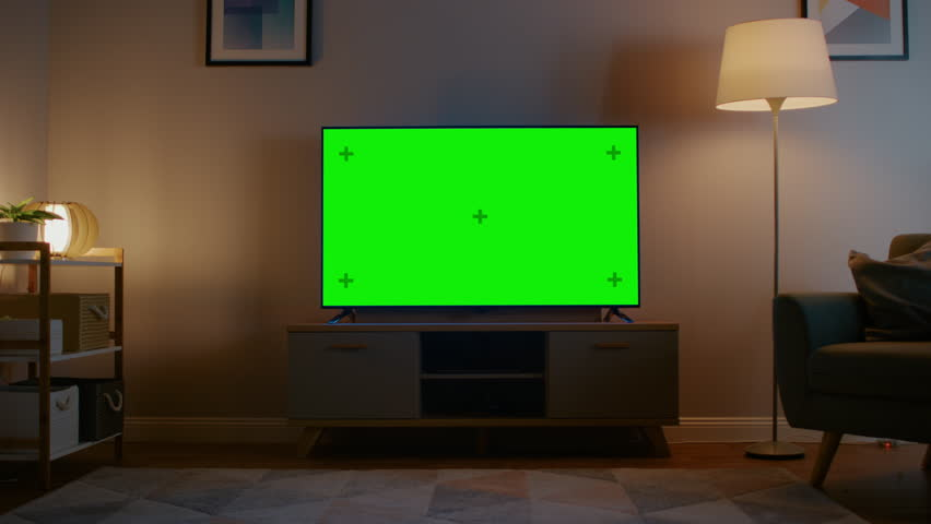 Zoom In Shot of a TV with Horizontal Green Screen Mock Up. Cozy Evening Living Room with a Chair and Lamps Turned On at Home. | Shutterstock HD Video #1023697381