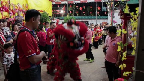 Kuil Kuno Johor Temple, Johor Bahru/Malaysia, February 4, 2019: Lion dance beside crowded people inside the temple during the celebration of Chinese New Year.