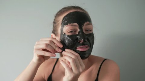 A young woman takes a black mask off her face. Close-up, slow motion. The mask slowly comes off the cheeks and nose. Model is smiling. Skin care