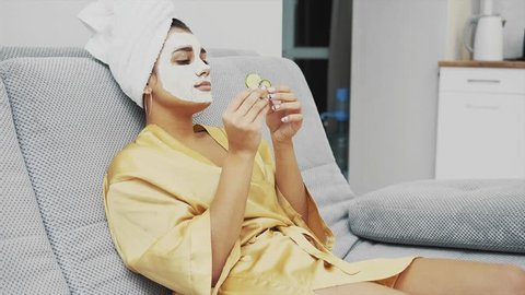A beautiful young woman gets a face mask in the spa center, lying with cucumbers in her eyes. Happy and gets a lot of fun. Smile