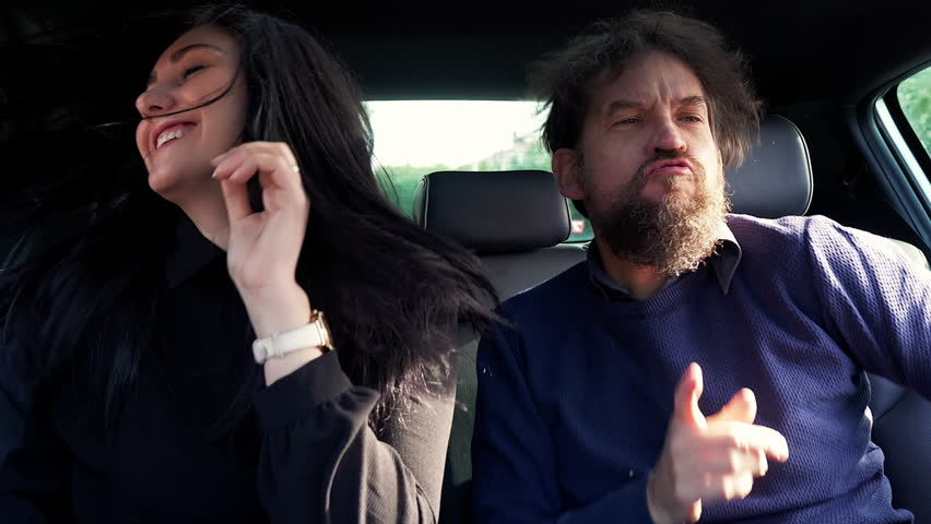 Happy man and woman shaking long hair dancing in car slow motion #1023888511