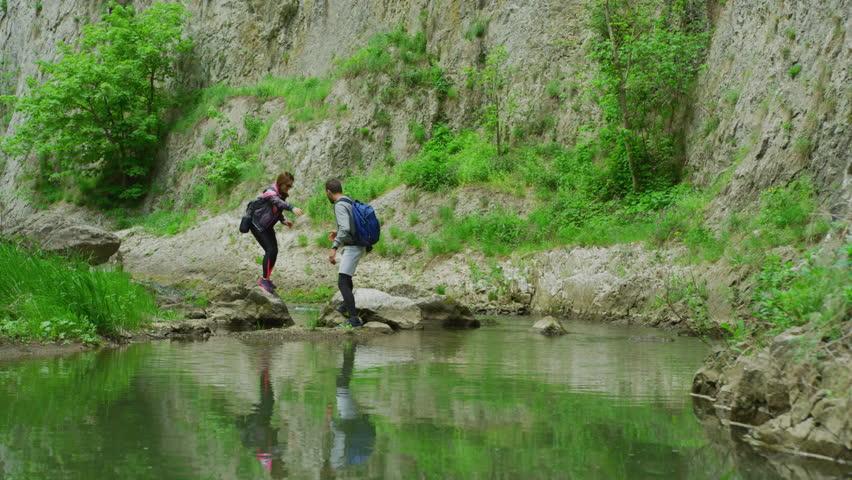 Man helping woman stepping on rocks. #1023900361
