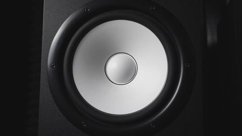Close up of moving modern sub-woofer on recording studio. White round audio speaker pulsating and vibrating from sound on low frequency. Work of high fidelity loudspeaker membrane. Slow motion