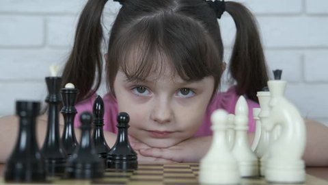 Portrait of a child with chess. Little girl with chess.