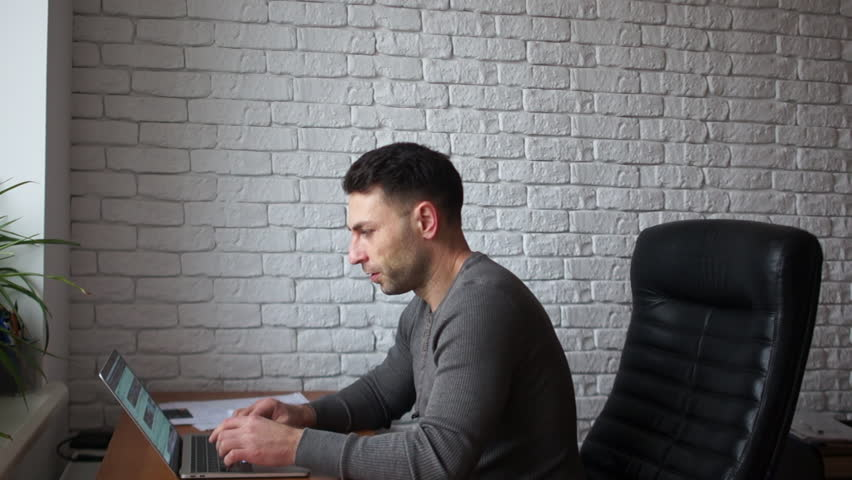 Handsome businessman working with laptop in office. A man sits in a leather chair against a white brick wall