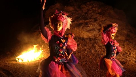 dancers girls in purple and pink dresses and gold masks are holding one hand on the belt, and the second over his head. At night with bonfires in the background